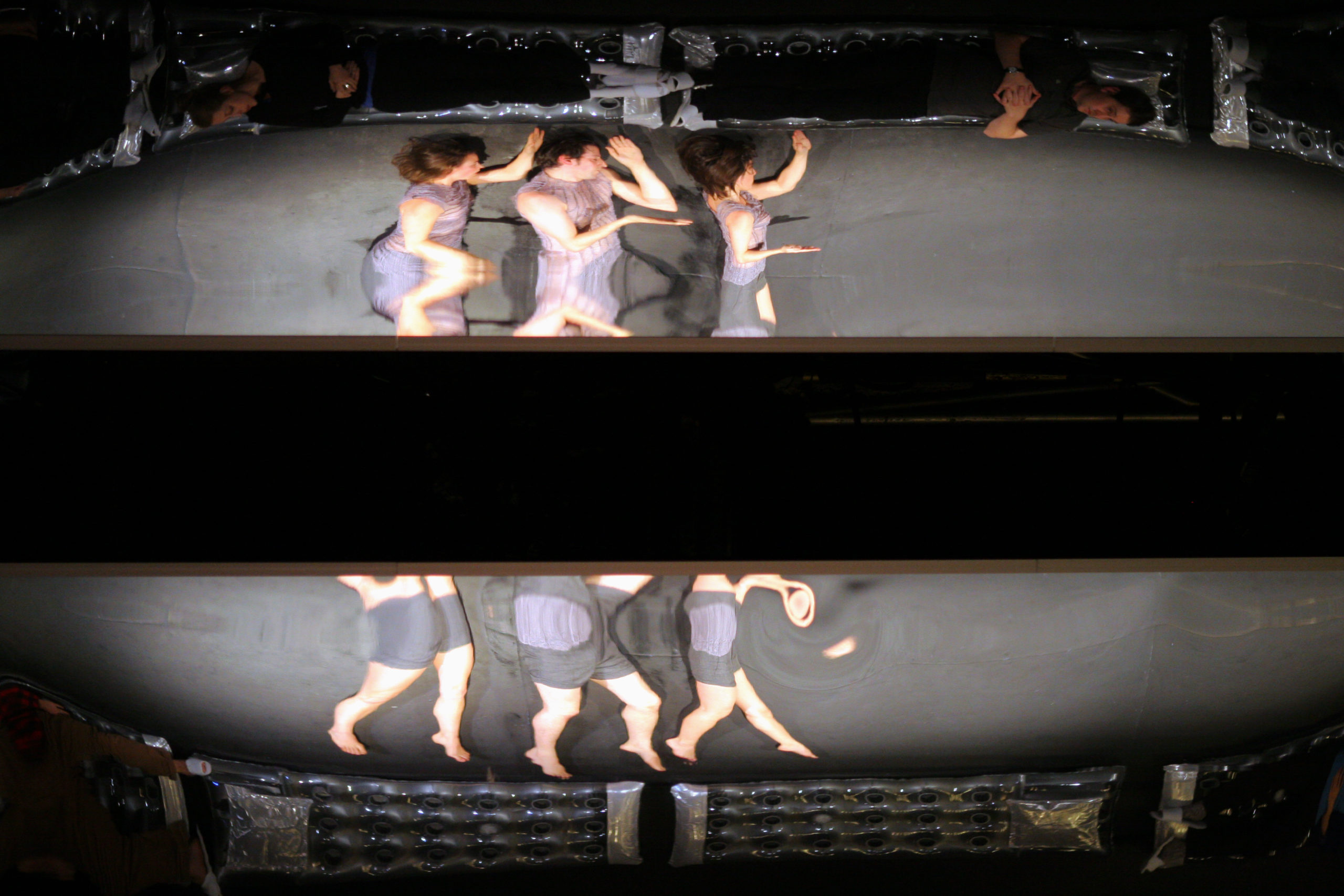 Distorted reflection of three dancers lying on their left side with a large black stripe in the middle of the photo