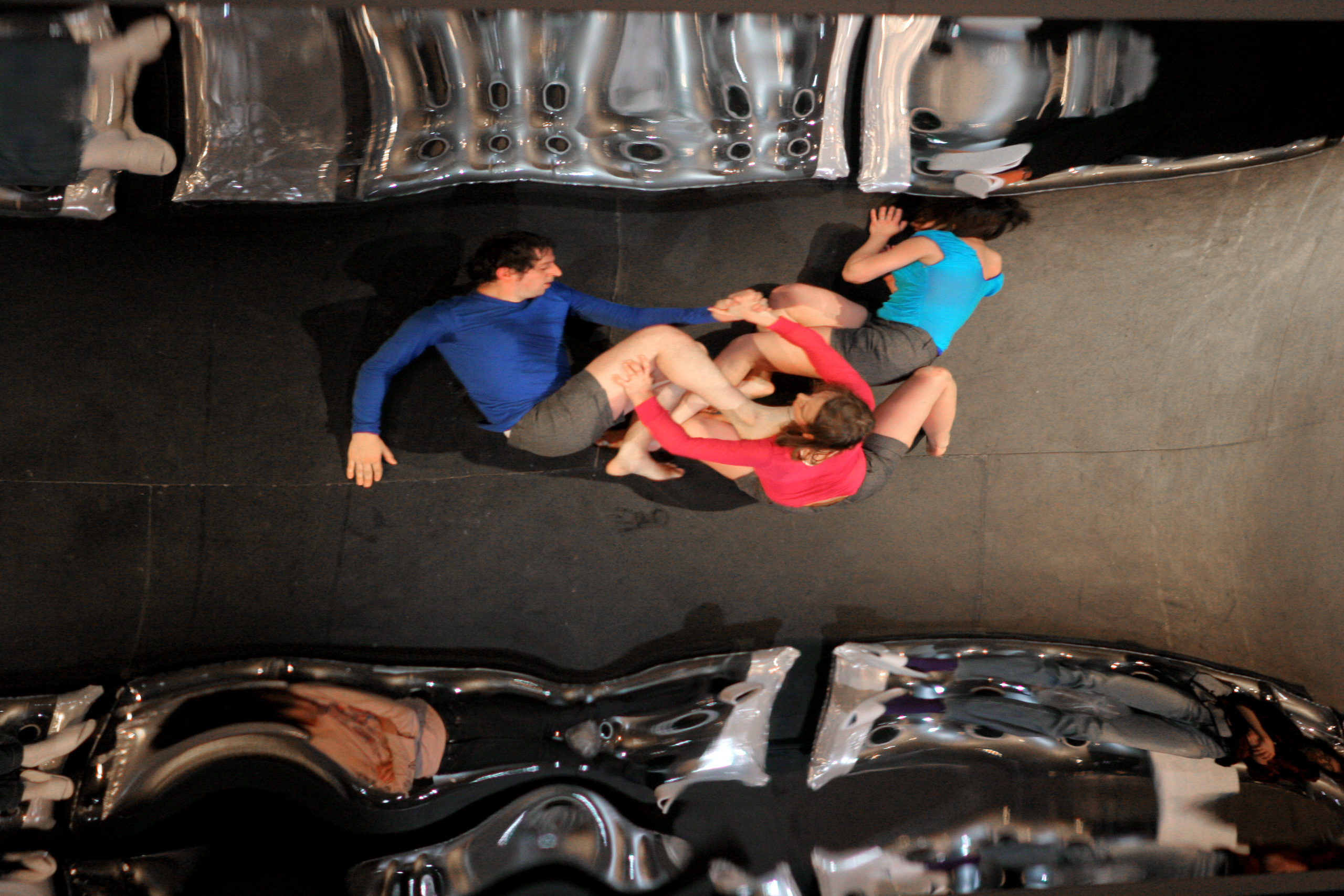 Distorted reflection of three dancers on the ground, limbs intertwined from a birds eye view